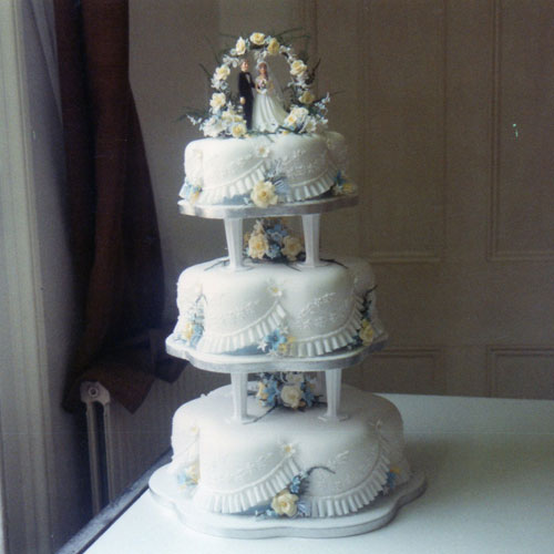 3 Tier Wedding Cake with Yellow Roses, Blue and White Blossoms and a ...